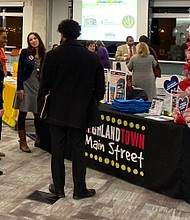 Baltimore Main Streets managers huddle around theHighlandtowninformation table to discuss ways to attract holiday shoppers to local neighborhoods during the15th annual Miracles on Main Streetskick-off eventat theBrown Advisory November 21, 2019 in Fells Point.