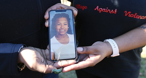 Kele A. Wright and Shavon M. Ragsdale hold a photo of Ms. Wright's daughter, Amiya Moses, 12, who was killed by a stray bullet in December 2015 as she played with other youngsters in North Side. Both women have lost loved ones to gun violence.