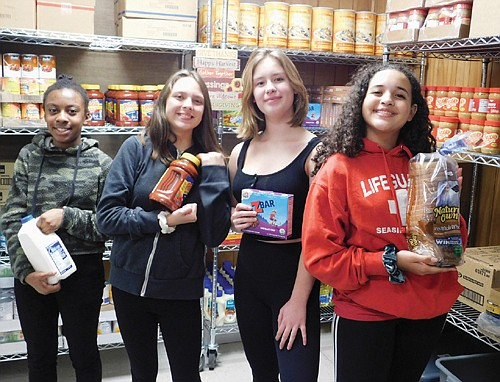 Students from Ockley Green Middle School in north Portland volunteer to help run the school's Dragon Mart, a free food bank benefiting kids who don't have enough to eat as well as assisting other families and people in the entire neighborhood. The students pictured are (from left) are Shamaya Daniels, Addyson Razo, Beatrice Pierson and Ilyarah Moteley.