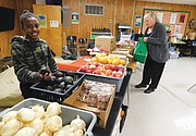 Ockley Green Middle School student Shamaya Daniels (left) checks out the avocados while volunteering at the north Portland school's new Dragon Mart, and resident Kay Cry picks up some items for Thanksgiving. The new free food bank serves students and the public.