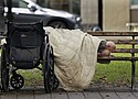 A person sleeps next to a wheelchair on a park bench, downtown. (AP file photo)