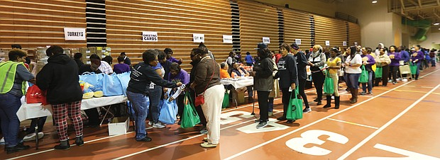 Because of the volunteer effort, hundreds of people moved smoothly through the line at the Arthur Ashe Jr. Athletic Center to take home turkeys, canned goods and the trimmings for Thanksgiving.