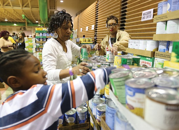 Chandle Brooks, 7, helps to organize canned vegetables with his aunt, Charlene Taylor, center, and Tawana Ferguson at Operation Harvest, a community Thanksgiving food distribution effort launched three years ago by St. Paul's Baptist Church. This is the third year for the effort that has drawn support from dozens of organizations and companies across the area and more than 400 volunteers.