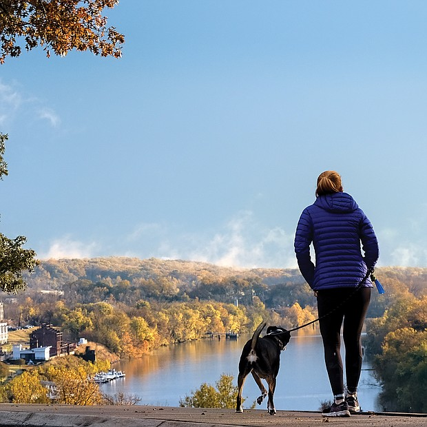 A woman and her dog pause to drink in an iconic view of the James River from Libby Hill Park in the East End. Legend has it that the city's founder, William Byrd II, named Richmond after the English borough of Richmond-upon-Thames because the bend of the James River at this vantage point reminded him of the Thames River in its passage through that London suburb. No evidence has ever turned up to support the story.