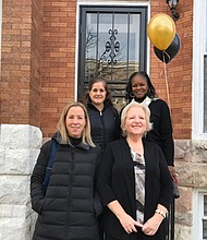 L-r: Amanda Owens, Abell Foundation; Ginny Robertson, President of the Light of Truth board of directors; (back row left to right) Elizabeth Perriello Rice, France Merrick Foundation; and  Betty Scott, Peer Housing Specialist LTC. They are standing  in front of the 933 W. Lafayette Avenue location.