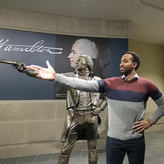 "Cast members from the Richmond tour of ""Hamilton"" get a behind-the- scenes tour of the Virginia Museum of History & Culture last Friday where they had an opportunity to see historical artifacts related to the characters they portray. Edred Utomi, who portrays the musical's name character, Alexander Hamilton, strikes a pose immortalized by the museum's Hamilton sculpture in the infamous duel with Aaron Burr."