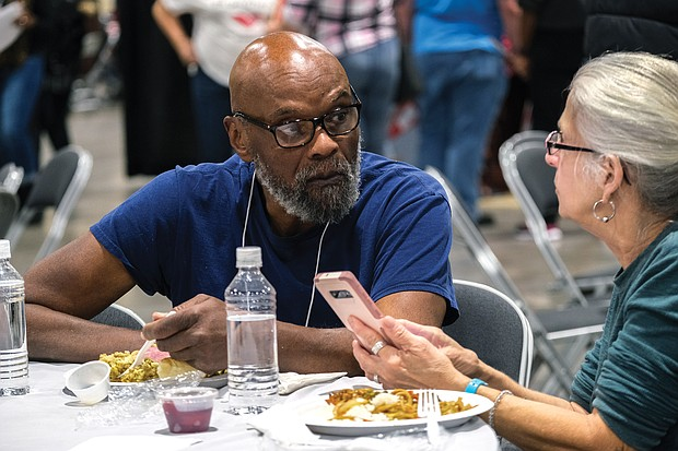 Booker Hargrove and Karen Knarr take a break from volunteering as coat checkers to savor a meal.