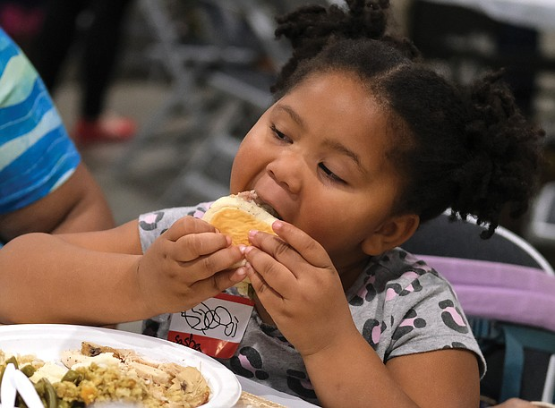 Sasha Northan, 4, takes a bite from a dinner roll.