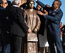 Montgomery, Ala., Mayor Steven Reed, right, and Alabama Gov. Kay Ivey, front left, work with others to unveil the statue of civil rights icon Rosa Parks in downtown Montgomery last Sunday, the anniversary of her 1955 arrest for not giving up her seat on a public bus.