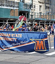 Holding the MSU Magificient Marching Machine banner are Marquis Bailey