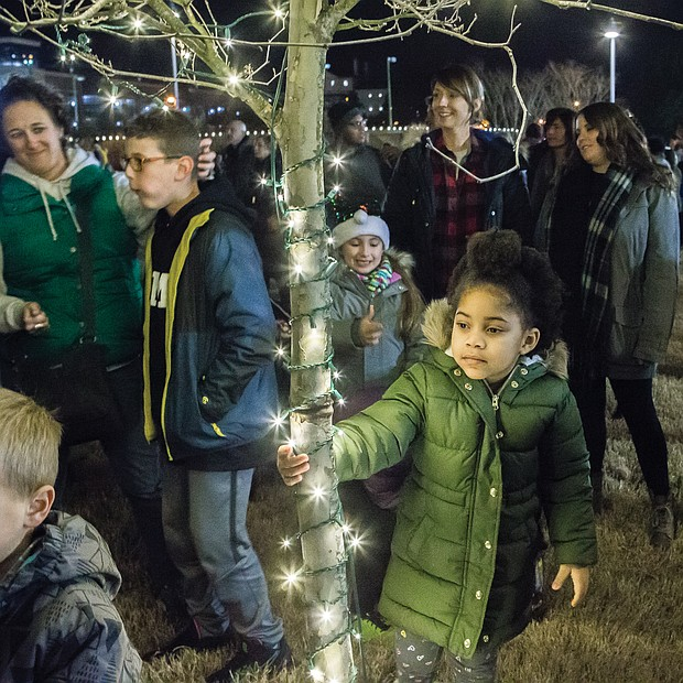 Eden Boyce, 5, hangs on to a tree decorated with lights during the festivities.