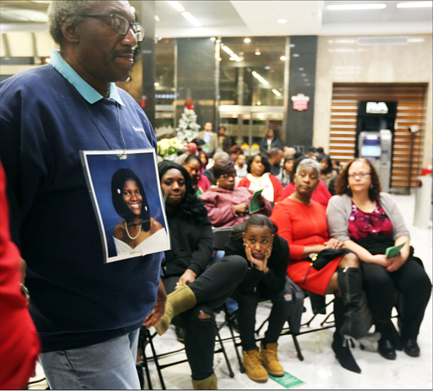 """John Burnley of Richmond, below, wears a photo of his late daughter, Juanita Burnley, during the Coalition Against Violence's 29th Annual Holiday Memorial Service to remember those who lost their lives to violence in the city. Relatives, friends and supporters mourning lost loved ones who were victims of violence at- tended the Dec. 12 ceremony held in the lobby of Richmond City Hall. Participants wrote the names of their loved ones on red ribbons that were placed around the statue, """"River of Tears,"""" that stands situated in City Hall. Mr. Burnley's daughter was murdered by her boyfriend in No- vember 2007, and he has annually attended the memorial started by Linda Jordan to help family members with their grief and loss through the holidays."""