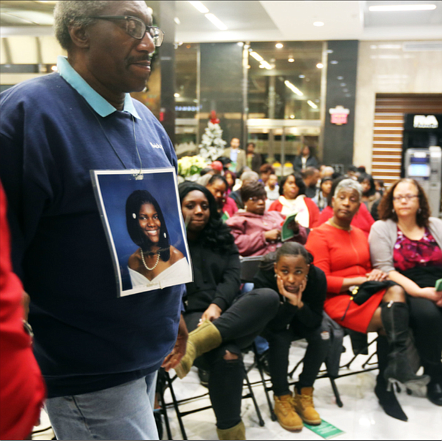 John Burnley of Richmond, below, wears a photo of his late daughter, Juanita Burnley, during the Coalition Against Violence's 29th Annual Holiday Memorial Service to remember those who lost their lives to violence in the city. Relatives, friends and supporters mourning lost loved ones who were victims of violence at- tended the Dec. 12 ceremony held in the lobby of Richmond City Hall. Participants wrote the names of their loved ones on red ribbons that