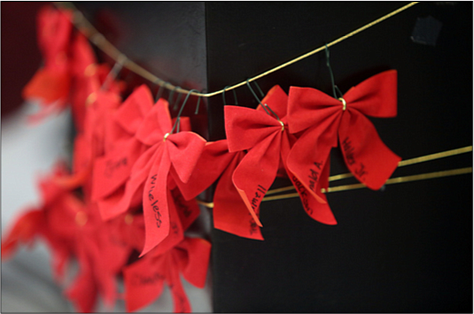 """Participants wrote the names of their loved ones on red ribbons that were placed around the statue, """"River of Tears,"""" that stands situated in City Hall."""