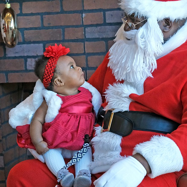 Ayla Hyndman, 6 months, is giving Soul Santa a close examination as if to determine if she can tell him all of her Christmas wishes. This is the first Christmas for Ayla, who visited Soul Santa, aka Floyd Brown, recently with her parents at the Black History Museum and Cultural Center of Virginia. Soul Santa has become an annual tradition at the museum in Jackson Ward.