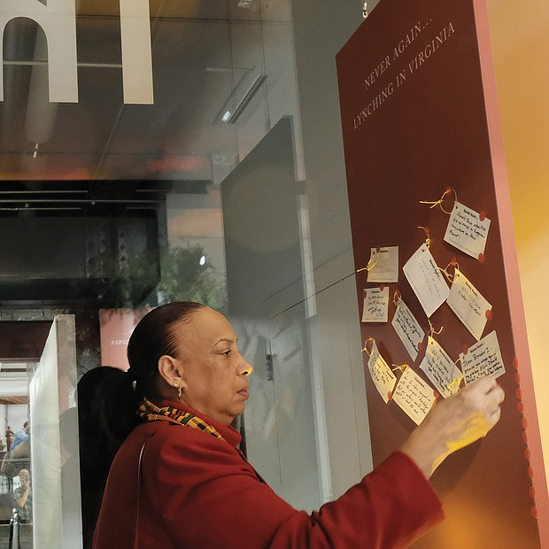 Former Richmond Judge Birdie H. Jamison, right, places a note with her thoughts about the exhibit on a public thought board.