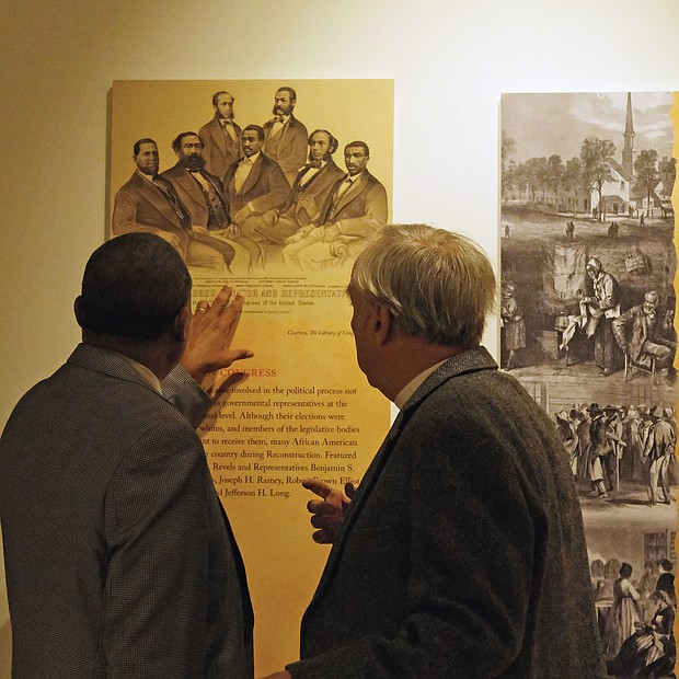 Rev. Sylvester Turner and the Rev. Ben Campbell, both of whom serve on the Richmond Slave Trail Commission discuss one of the panels in the exhibit.