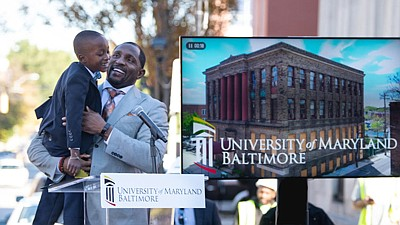 Pro Football Hall of Famer, Ravens legend, and new UMB Foundation board member Ray Lewis brings second-grader Blair Pinnacle, III onto the stage at the ceremonial groundbreaking of UMB's new Community Engagement Center.