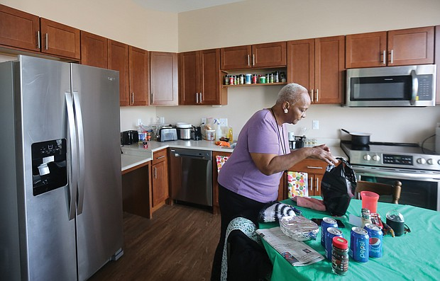 Ms. Ward unpacks groceries in her new kitchen, while Ms. Cavell shows off her new living room and bedroom. The two, who had lived for 35 years in the nearby Creighton Court public housing community are among 37 seniors from Creighton Court who have moved into the newly completed building as part of the first step to redeveloping the public housing complex. The Community Builders of Boston undertook the Armstrong Renaissance development with the Richmond Redevelopment and Housing Authority.