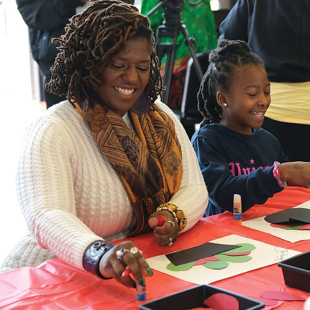 Tiya Shaw, left, works with her 7-year-old daughter, Shawn, on a harvest craft project in the festival's area for youths.