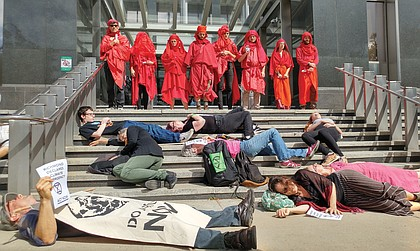 """Members of Extinction Rebellion Richmond stage a silent die-in on the steps of City Hall in October to call attention to the need to act to abate climate change. Looking on are members who call themselves the """"Red Rebel Brigade."""""""