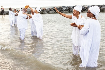 Queen mothers from the Institute of Whole Life Healing in Kentucky anoint people during a sunrise cleansing and healing ceremony at Buckroe Beach in Hampton as part of the August events commemorating the 400th anniversary of the first Africans arriving via slave ships in English North America.