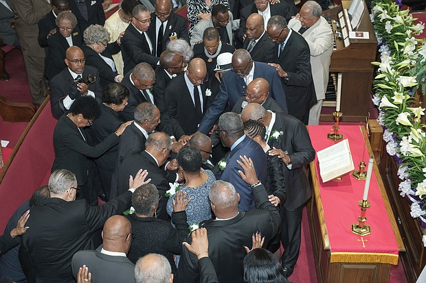 "Capping the April installation of Dr. William Eric Jackson Sr. as the ninth pastor of Fourth Baptist Church, visiting ministers and church deacons participate in a ""laying of hands"" ceremony with Dr. Jackson, seated, in the sanctuary of the historic Church Hill congregation."