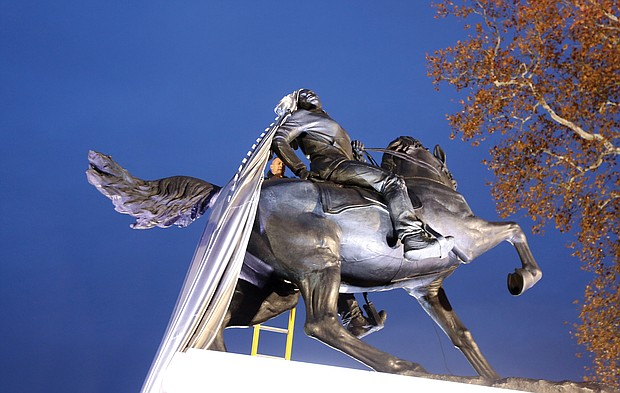 """Richmond Firefighter John Lukhard works to remove a drape caught on the hair of Kehinde Wiley's """"Rumors of War"""" sculpture during an unveiling ceremony in December at the Virginia Museum of Fine Arts."""