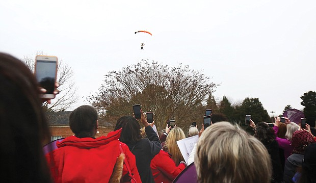Three members of the Women's Skydiving Network parachute into Lewis Ginter Botanical Garden Tuesday morning to the clicks of dozens of cell phone cameras as they helped launch the Women's Equality Legislative Summit.
