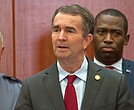 Gov. Ralph S. Northam, center, is given a unified show of support during Wednesday's news conference by State Police Superintendent Gary Settle, left, Richmond Mayor Levar M. Stoney and other state law enforcement officials.