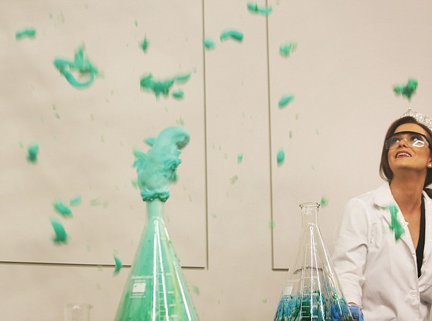 """Miss America 2020 Camille Schrier stands back as her """"elephant toothpaste"""" experiment erupts as planned with blue and green foam during a demonstration Wednesday for Carver Elementary School students at the Science Museum of Virginia."""
