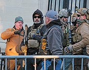Men dressed in full military gear and carrying firearms stand in front of the state Supreme Court Building on 9th Street across from Capitol Square.
