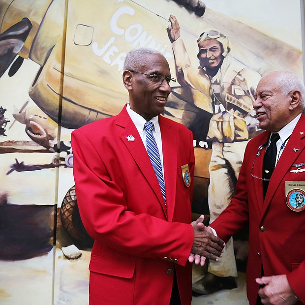 Rep. A. Donald McEachin of Richmond, left, is congratulated by Howard L. Baugh of Portsmouth after the con- gressman was made an honorary Tuskegee Airman during a ceremony last Saturday by the Howard Baugh Chapter of Tuskegee Airmen Inc. in Petersburg. Mr. Baugh is the oldest son of the late Lt. Col. Howard Baugh of Petersburg who was one of the famed airmen of the 99th Pursuit Squadron and the 332nd Fighter Group that escorted bombers on combat missions over Europe during World War II. Lt. Col. Baugh was honored during his lifetime with numerous commendations, including the Distinguished Flying Cross, the Air Medal with three Oak Leaf Clusters and the U.S. Air Force Commendation Medal, along with the French Legion of Honor Award bestowed by the French government. The ceremony was held at the Richmond Executive Airport in Chesterfield County. The Petersburg group is one of 56 Tuskegee Airmen chapters in the United States dedicated to honoring the accomplishments and preserving the legacy of the airmen who trained at the Tuskegee