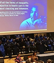 Dr. Sherita Hill Golden, Vice President and Chief Diversity Officer for Johns Hopkins Medicine, and Dr. Valerie Montgomery Rice, President and Dean of the Morehouse School of Medicine during the 38th Annual Martin Luther King, Jr. Commemoration program. Unified Voices of Johns Hopkins is seated behind them.