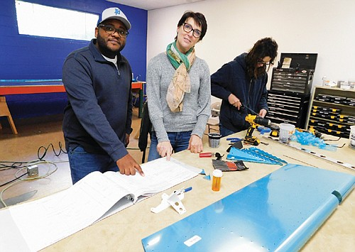 Johnell Bell (left) and Julia Cannell oversee a free aviation and aeronautics training program for young people of color and low income students at the Airway Science for Kids, now located in the former Albina Youth Opportunity School.  Pictured at right is McKinzie Ried, one of the school's aviation students, working on a project.