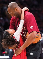 Kobe Bryant hugs his daughter, Gianna, on the basketball court during warm-ups before an NBA All-Star Game in Toronto on Feb. 14, 2016.