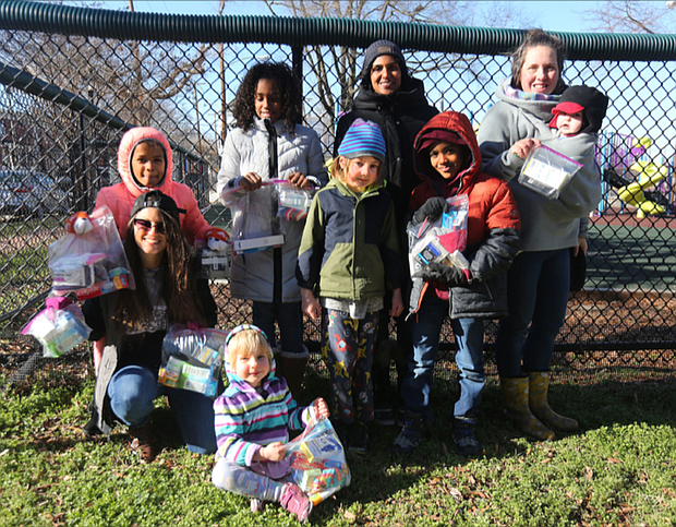 Ashley Smith-O'Meara, seated left, wants people to feel free to receive help without judgment or condition. She and other parents and children from the FERNNS Homeschool Co-op volunteering with the Walls of Love project in Richmond show off bags packed with personal items that will be put on the fence at Abner Clay Park in Jackson Ward. With her are, standing from left, her daughter, Sofia Ruffin, 9; Asfana Dawkins, 9; parent Umerah Mujahid; Sam Outland-Brock, 7; Jahid Dawkins, 8; parent Joy Outland-Brock holding her year-old daughter, Florence Outland-Brock; and seated front, Felicity Outland-Brock, 4.