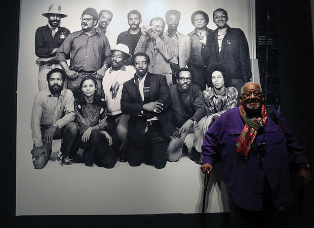 Shawn Walker, who was a member of the Kamoinge collective established by the late Henrico County native Louis Draper in New York City in 1963, stands in front of a historic photo of the group,  The exhibit will be on view through June 14 at the museum, 200 N. Arthur Ashe Blvd.