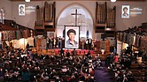 People applaud and take photos during the unveiling ceremony Jan. 30 for the new U.S. Postal Service Black Heritage series stamp honoring the late journalist Gwen Ifill. The ceremony took place at the church she was a member of, Metropolitan African Methodist Episcopal Church in Washington.