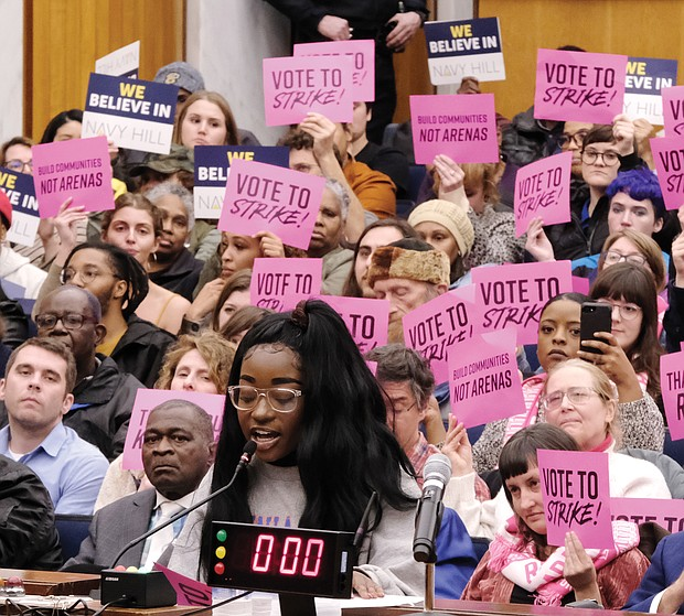 Naomi Isaac urges Richmond City Council to kill the $1.5 billion Coliseum replacement plan at Monday's meeting. She was among a long line of people speaking on the proposal before council voted to scrap it. Behind her, supporters and opponents of the plan hold up signs reflecting their views.