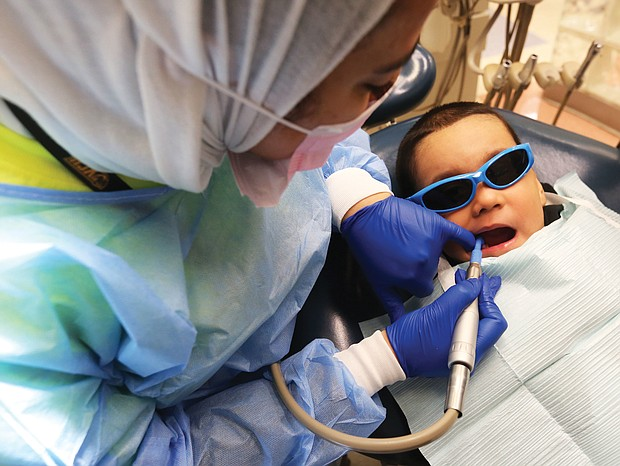 """Bayron Rosales, 3, opens wide as Dr. Taibah AlBaker works on his mouth during VCu Dental Care Pediatric Dentistry's annual day of free dental care last Friday at the Lyons Dental Building on 12th Street in Downtown. The effort was part of the American Dental Association's annual """"Give Kids A Smile"""" program begun in 2003 in which dentists, dental hygienists and dental assistants around the country volunteer their time and talents to provide free care to youngsters who otherwise would not have access to a dentist. In Richmond, pediatric dental specialists offered exams, cleanings, X-rays, fillings, extractions and minor restorations to youngsters without dental insurance. The national program kicks off National Children's Dental Health Month."""