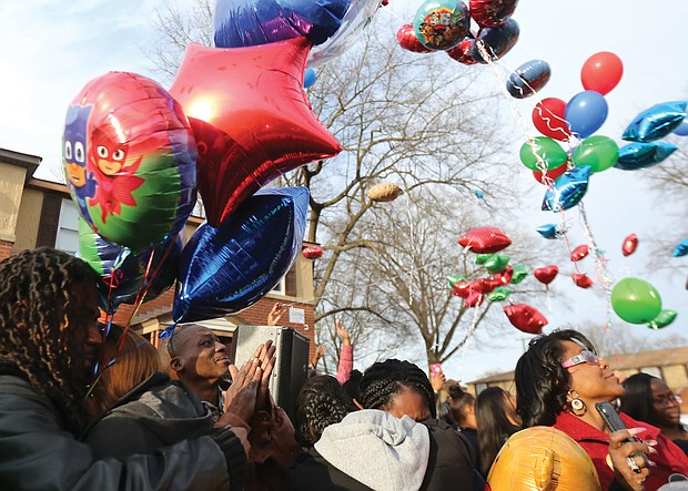 Dozens of people release colorful balloons in memory of 3-year-old Sharmar Hill Jr. during a prayer vigil last Saturday outside his family's home in the 1700 block of Southlawn Avenue in Hillside Court. The youngster was shot and killed Feb. 1 as he played outside his home in the South Side public housing community.