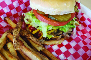 The Junkie Burger, which has vegan American cheese, smashed avocado, sautéed mushrooms and grilled onions, crispy onion strips, lettuce, pickles, tomato, with a garlic and onion aoli, is one of Plant Based Junkie Owner Bobbie Beaugard's favorite menu items. Photo Credit: Bobbie Beaugard.