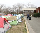 A resident of Cathy's Camp on Oliver Hill Way rolls his belongings next to a row of tents. To the right is the Annie Giles Community Resource Center, the city's winter shelter. The center also was open during the day this week for residents to meet with staff from nonprofits, the city and a mental health agency as part of an outreach effort to help provide needed services.