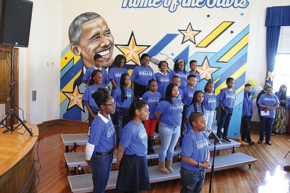 """The Barack Obama Celebration Choir sings an original song, """"O,"""" about the former president during last Friday's dedication ceremony. A mural by Richmond artist Hamilton Glass is behind them."""