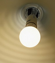 A LED bulb inside a white shade gives off a warm glow.