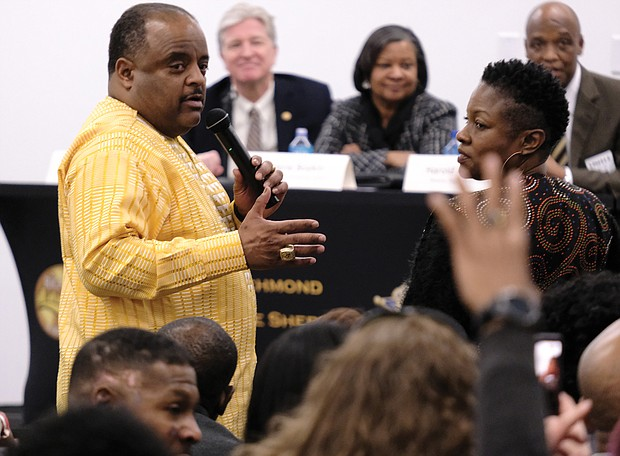 Moderator Roland S. Martin, left, takes a question from local radio host Clovia Lawrence during last Saturday's Justice Summit at the Richmond Justice Center. Looking on are several of the summit's nine panelists, Brian Moran, state secretary of public safety and homeland security; Valerie Boykin, director of the state Department of Juvenile Justice; and Harold W. Clarke, director of the state Department of Corrections.