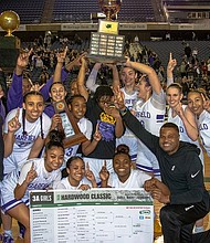 The Garfield High School girls 3A basketball team from Seattle celebrates after claiming the state 3A championship trophy by beating Lake Washington 55 to 41, Saturday, March 7 at the Tacoma Dome.