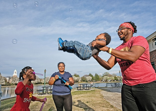 Shaun Yerby lifts his year-old son, Christian Moultrie, to catch bubbles blown by the youngster's mother, Catrina Moultrie, and 7-year-old aunt, Ja'niyah Jackson during an outing Wednesday at Fountain Lake in Byrd Park. The sunny, 68-degree day was a draw for people who headed outdoors. Temperatures are expected to be in the low 60s by the weekend.