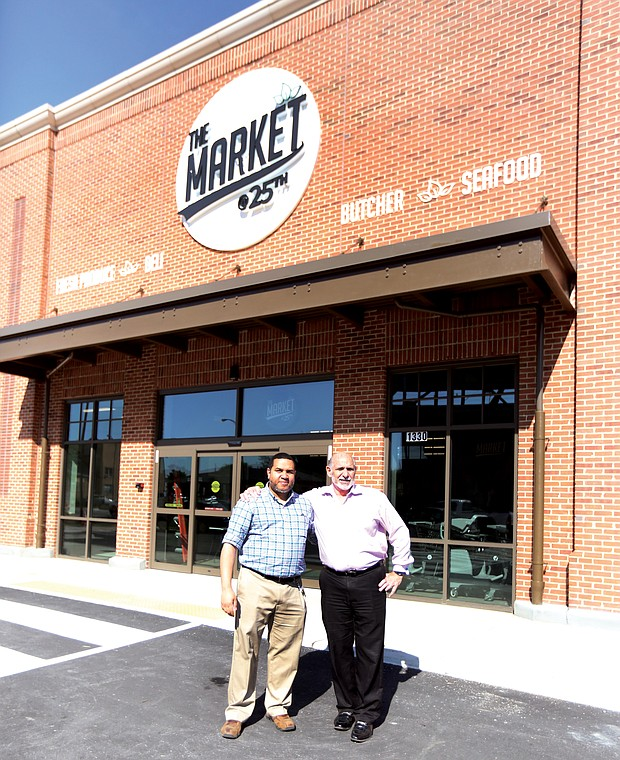 Norm Gold, right, developer and operator of The Market@25th, stands outside the grocery in Church Hill with store director Jae Scott before last April's grand opening.
